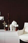 Gedrechselte Holzständer mit Kerzen auf weiss glänzendem Sideboard und Retrosessel