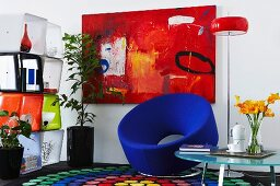 Sitzecke mit Sammlung poppiger 80er Jahre Möbel vor rotem Wandgemälde