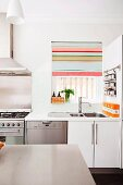 View over a table to a kitchen sink at a window, with a half-closed Roman blind with colorful stripes next to a gas oven in a modern kitchen