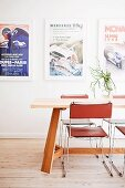 Delicate metal chairs with leather seats and backs around wooden table in front of framed posters on wall