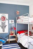 Metal-framed bunk beds in blue-painted teenagers' bedroom with drawings of motorbikes on wall