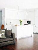 Blick auf weisse, offene Küche mit Kücheninsel