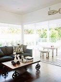 Wohnzimmerbereich mit Sofa, Couchttisch auf Rollen & geöffenten Schiebetüren zur überdachten Veranda