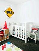 Kinderzimmer mit Gitterbett aus Holz, Spielzeugregal & Kinderteppich