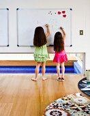 Zwei Mädchen malen an Magnetwand