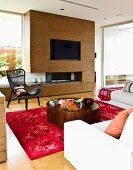 Wohnzimmer mit deckenhoher Schrankwand aus Walnussfurnier mit eingebautem Fernseher & Gaskamin