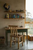 Rustic wooden chair and table in front of a concrete wall and book shelves next to a floor to ceiling window with a view