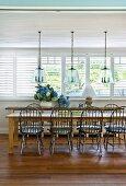Windsorstühle an rustikaler Esstafel in sonnigem Esszimmer