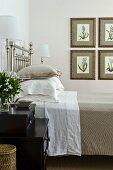 Edles Schlafzimmer mit versilbertem Bett und einer Sammlung gerahmter Blumenillustrationen an der Wand