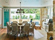 Sitzgruppe mit grossem, runden Tisch und Korbstühlen unter verspieltem Kronleuchter; beim Fenster ein Edelstahl Barbecue