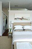 Modernes Gemälde über gestreiftem Bettkopfende in elegantem Schlafzimmer; im Hintergrund der begehbare Kleiderschrank