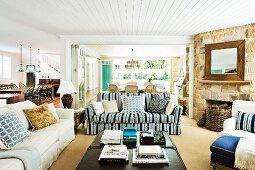 Weitläufiger Wohnraum im Hampton-Stil mit rustikaler Steinwand und offenem Kamin im Wohnbereich