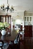 Lange Tafel und Holzstühle mit gerüschten Sitzkissen in offenem Wohnraum mit gediegener luxuriöser Einbauküche