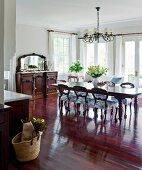 Rötlich schimmerndes Edelholz als vorherrschendes Material in offener Wohnküche mit Mobiliar im traditionellen Antikstil