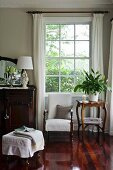 Traditioneller Sitzplatz am Fenster mit Polsterstuhl zwischen Spiegelkommode und Beistelltisch