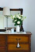 Weisser Blumenstrauss und Tischlampe auf antiker Kommode mit Spiegel