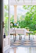 Blick durch offene Tür auf Terrasse mit Schachbrettfliesen und filigranen Drahtstühlen an weiss gedecktem Tisch
