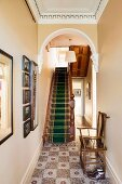Nostalgischer Fliesenboden im Flur mit Rundbogen vor Treppe mit Teppichläufer in einem herrschaftlichem Haus mit Stuckdecke