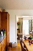 Esszimmer mit Holztisch gegenüber Büffet und Blick durch breiten Durchgang ins Wohnzimmer