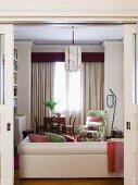 Blick durch offene Schiebetür auf helle Polstercouch und geblümten Sessel in Loungebereich vor Fenster mit bodenlangem Vorhang