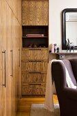 Lesesessel vor eingebautem Schrank mit Holzfurnier in Wohnzimmerecke