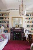 Violetter Teppich vor offenem Kamin zwischen Bücherregalen und Couch gegenüber Essplatz