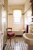 Blick durch offene Tür auf antiken Holzstuhl und gemusterten Fliesenboden im Vintage Bad