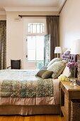 Doppelbett mit eleganter Tagesdecke und passenden Kissen neben offener Balkontür in traditionellem elegantem Schlafzimmer