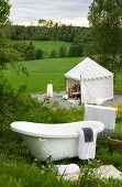 Vintage bathtub on mountain slope and view of tent-like pavilion in green meadow