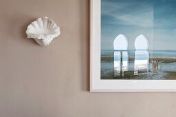 Shell-shaped sconce lamp next to framed picture with reflection in glass on pale grey wall