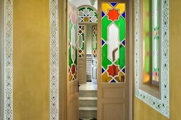 Foyer with stencilled painting on ochre yellow walls and stained glass panels in open door with view into hallway