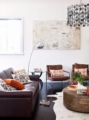 Seating area with leather sofa, retro armchair and designer lamps in open-plan interior