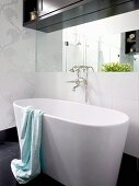 Free-standing designer bathtub with retro tap fittings; dark wood bathroom cabinet above wall-mounted mirror
