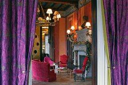 Blick durch violette Vorhänge in prunkvollen Renaissance Salon mit roten Polstermöbeln vor dem Kamin