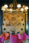 Raumhoch an einer Wand applizierte Uhr mit Mondphasen und Sternzeichen; pinkfarbene Polsterstühle im Vordergrund