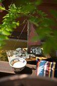 Schale neben Kissen auf Holzbank und selbstgebautes Miniatur Segelboot im Wasserbecken