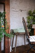 Pastel green tray on vintage stool against rustic wall in conservatory