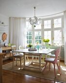 Lattice bay window in sunny kitchen-dining room with table, vintage chairs and natural fibre rug