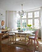 Erker mit Sprossenfenstern in sonniger Wohnküche mit Tisch, Vintage Stühlen und einem Teppich aus Naturfasern
