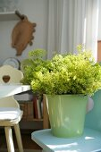 Pastellgrüner Eimer mit gelbem Sommerblumenstrauss auf Bauernstuhl