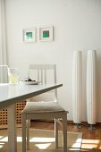 Zwei moderne Stehlampen an weisser Wand in sonniger Küche; im Vordergrund ein einfacher Esstisch und ein Vintage Stuhl mit Sitzkissen