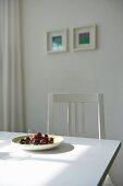 Ein Teller mit frischen Kirschen auf weißem Esstisch in sonniger Küche