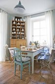 Various chairs around old table in front of window