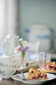Vintage crockery and damson cake on set table