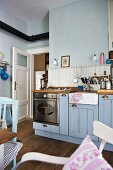 Gas cooker and ceramic sink in blue country-house kitchen