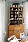 Old crockery in compartments on top of old wooden kitchen dresser