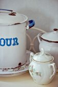 Vintage floral sugar bowl in front of enamel pots