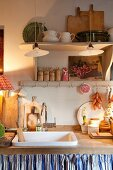 Holzarbeitsplatte mit Trogbecken und dekorierten Küchenutensilien in Landhausküche