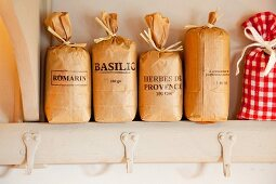 Beschriftete Papiersäcke mit Kräutern im Küchenregal