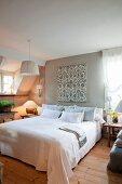 Doppelbett in Schlafzimmer unterm Dach mit romantischer Landhausdeko